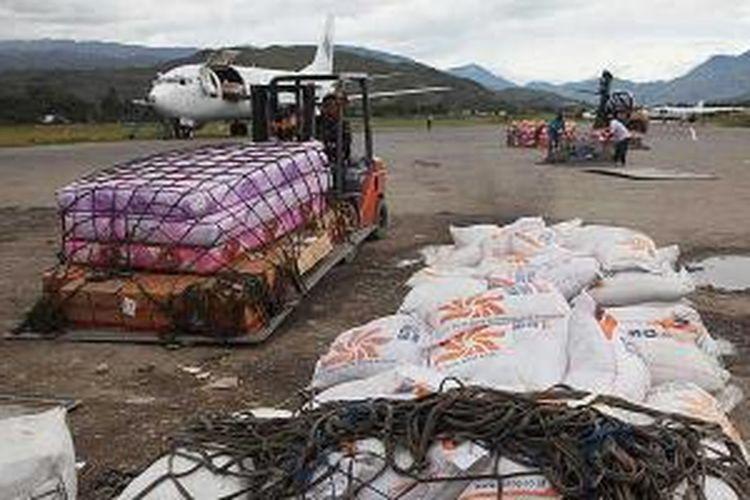 Beras yang telah diturunkan dari pesawat kargo di Bandara Wamena, Jayawijaya, Papua, siap diangkut menuju gudang, Rabu (11/12/2013). Selain melemahkan budaya bertani warga Papua, pasokan beras miskin juga rawan diselewengkan.