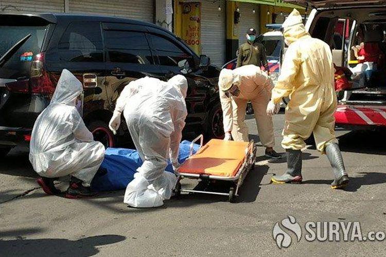 Anggota Tim Inafis Polrestabes Surabaya saat mengevakuasi jenazah korban wanita yang meninggal dalam mobil taksi online di Jalan Siwalankerto, Siwalankerto, Wonocolo, Surabaya, Selasa (12/5/2020).