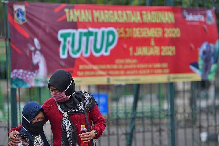 Warga meninggalkan Taman Margasatwa Ragunan yang tutup di Jakarta Selatan, Jumat (25/12/2020). Pemerintah Provinsi DKI Jakarta menutup area publik dan sejumlah tempat wisata termasuk Taman Margasatwa Ragunan selama masa libur perayaan Hari Natal dan Tahun Baru pada 25 dan 31 Desember 2020, serta 1 Januari 2021.