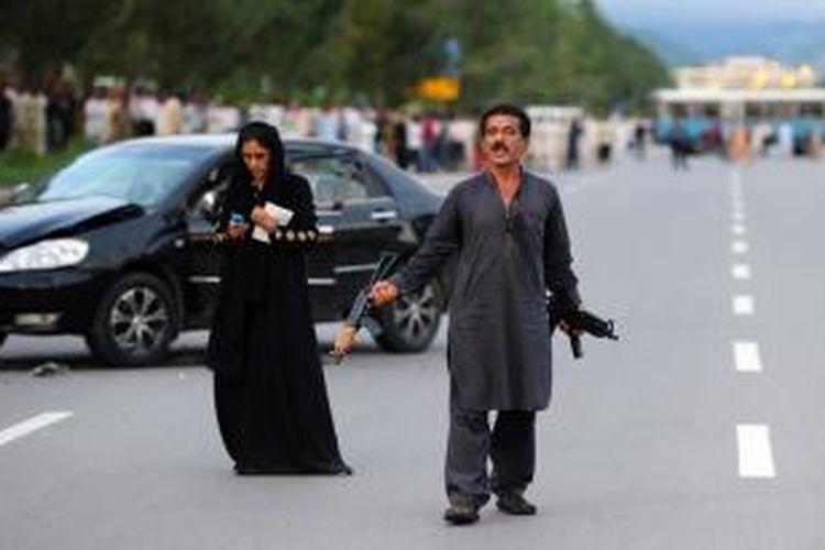 Muhammad Sikandar, sambil membawa dua senapan otomatis meneriakkan tuntutannya di sebuah ruas jalan utama kota Islamabad, Pakistan, tak jauh dari kantor presiden dan gedung parlemen. Sementara di belakangnya, sang istri mencatat semua perkataan suaminya untuk disampaikan kepada negosiator kepolisian.