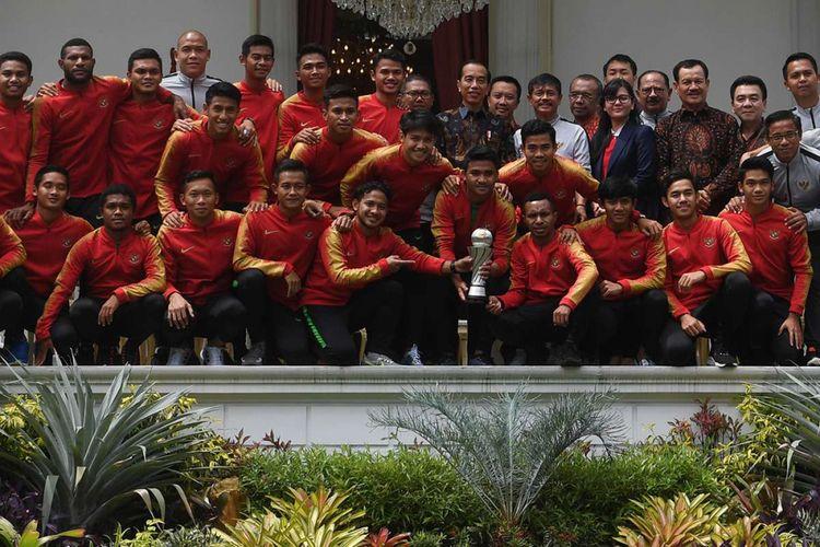 Presiden Joko Widodo (tengah) berfoto dengan pemain Timnas U-22 Indonesia serta ofisial di beranda Istana Merdeka, Jakarta, Kamis (28/2/2019). Presiden memberikan bonus kepada pemain timnas U-22 yang menjadi juara pada kejuaraan AFF U-22 setelah mengalahkan Thailand dengan skor 2-1 dan  berharap Garuda Muda untuk meningkatkan prestasi selanjutnya dengan menjuarai AFC dan Sea Games.