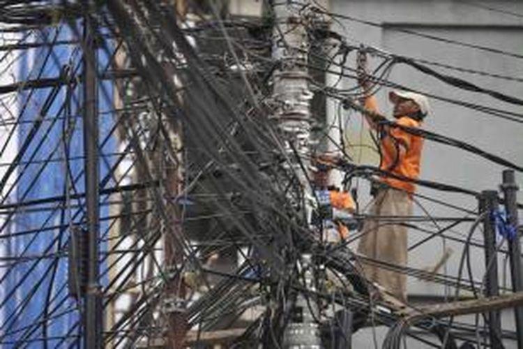 Petugas memasang sambungan baru kabel listrik PLN sebuah perkantoran di Jalan Budikemulyaan, Jakarta Pusat, Rabu (21/8/2013).