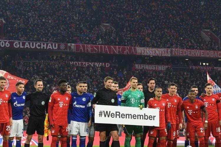 Pemain Bayern Munchen, Schalke 04 dan wasit memegang plakat bertuliskan Kami ingat, pada kesempatan pembebasan kamp konsentrasi Auschwitz 75 tahun yang lalu, sebelum pertandingan Bundesliga divisi pertama Jerman antara FC Bayern Munich dan FC Schalke 04