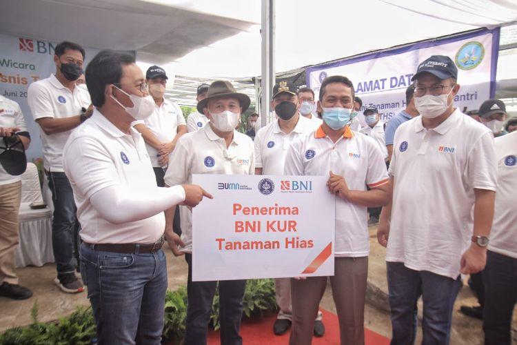 Direktur Hubungan Kelembagaan BNI Sis Apik Wijayanto (kiri) menyerahkan secara simbolis Kredit Usaha Rakyat (KUR) kepada petani tanaman hias binaan IPB yang disaksikan oleh Menteri Koperasi dan UMKM Teten Masduki (kedua kiri) dan Rektor IPB Arif Satria (kanan) di Bogor, Jawa Barat (Minggu, 6 Juni 2021). Selain pembiayaan murah melalui KUR, BNI juga memberikan kemudahan transaksi kepada petani binaan IPB berupa pembayaran melalui QRIS di aplikasi BNI Mobile Banking.