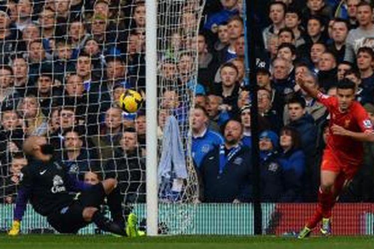 Pemain Liverpool Phillippe Coutinho mencetak gol ke gawang Everton yang dijaga Tim Howard dalam pertandingan Liga Inggris antara Everton kontra Liverpool di Stadion Goodison Park, Sabtu (23/11/2013).