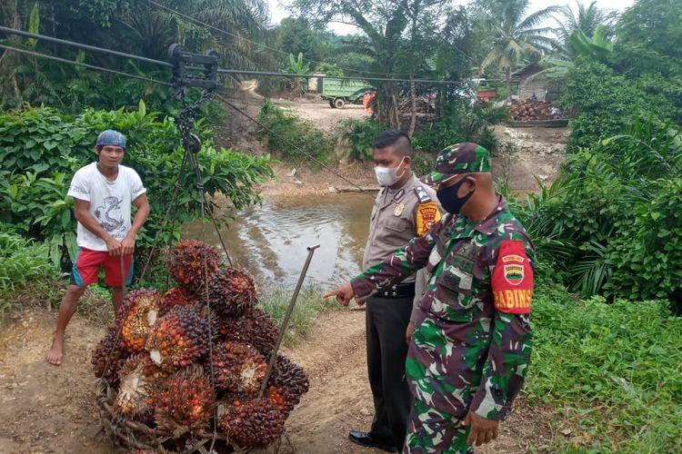 Babinsa Koramil 05/Kampar Kiri, Serma Karyawanto bersama kepolisian memperlihatkan tempat penyeberangan sawit yang digunakan anak SD untuk menyeberang di Desa Kuntu Darussalam, Kecamatan Kampar Kiri, Kabupaten Kampar, Riau, Jumat (11/6/2021).