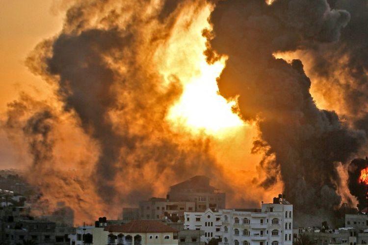 Kebakaran mengamuk saat matahari terbit di Khan Yunish menyusul serangan udara Israel terhadap sasaran di Jalur Gaza selatan, pada awal 12 Mei 2021.