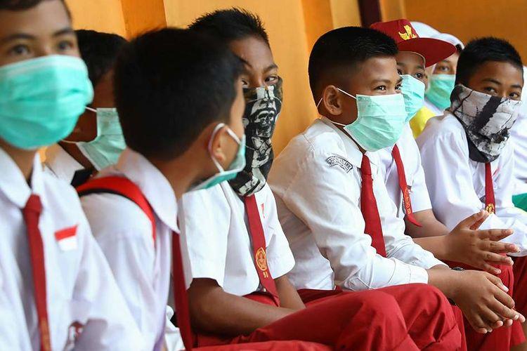 Siswa sekolah dasar di Natuna, Kepulauan Riau, mengenakan masker saat berada di area sekolah mereka, Selasa (4/2/2020). Hampir seluruh warga di Natuna menggunakan masker menyusul keputusan Pemerintah RI untuk menempatkan WNI yang dievakuasi dari Wuhan, China, di pulau tersebut.