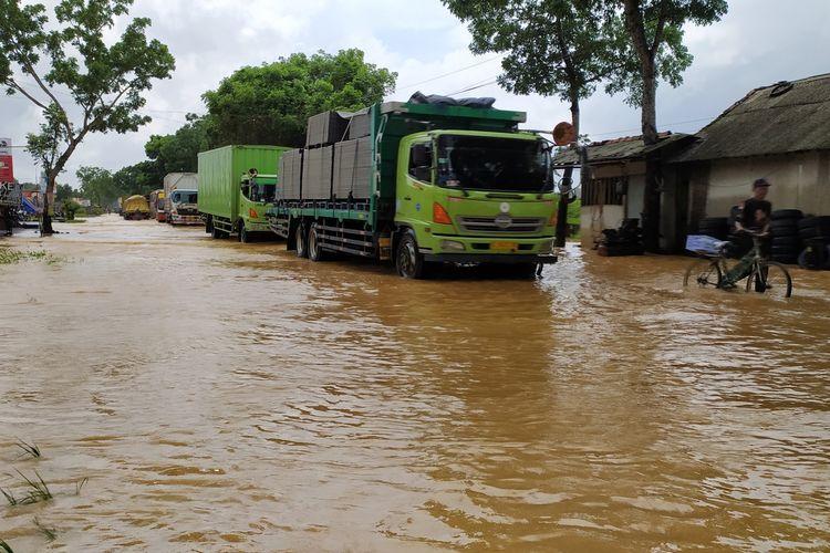 Kendaraan berjalan pelan melintasi genangan banjir di ruas jalan nasional Desa Kedungpring, Kecamatan Kemranjen, Kabupaten Banyumas, Jawa Tengah, Selasa (17/11/2020).
