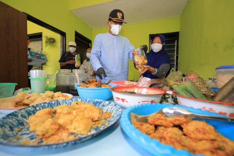 CEK MAKANAN—Walikota Madiun, Maidi mengecek makanan yang akan diantar PKL ke warga isoman di Kelurahan Kanigoro, Kecamatan Taman, Kota Madiun, Jawa Timur