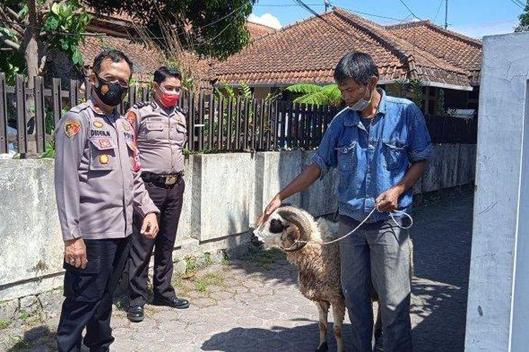 Kapolsek Garut Kota Kompol Deden Mulyana (kiri) saat menyerahkan domba untuk kurban kepada Yadi Supardi (kanan).