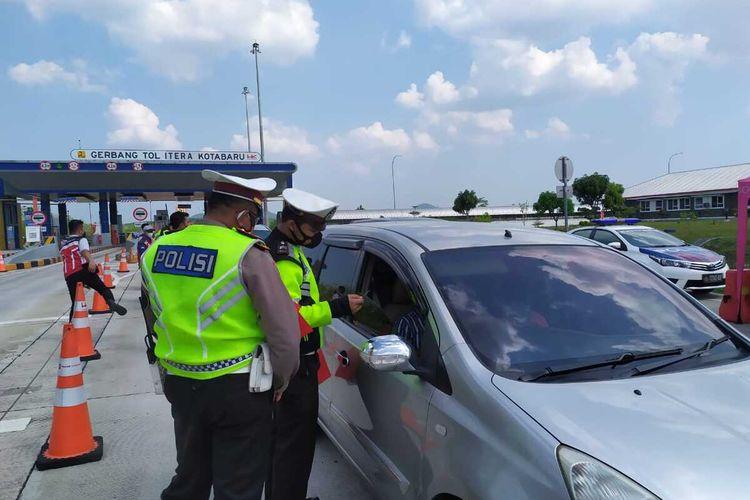 Petugas Ditlantas Polda Lampung memeriksa kelengkapan syarat perjalanan bagi pengendara di Jalan Tol Lampung.
