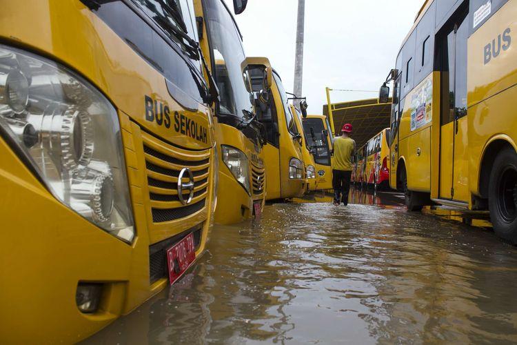 Petugas mengecek bus sekolah yang terendam banjir di Jl. Raya Pondok Gede, Kramat Jati, Jakarta Timur, Rabu (1/1/2020). Luapan air Kali Baru sebabkan wilayah Kramat Jati terendam hingga sebahu orang dewasa.