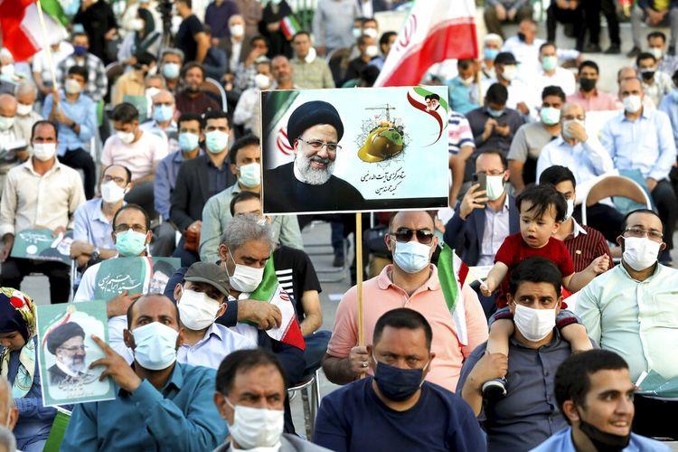 Pendukung calon presiden Ebrahim Raisi memegang poster dalam reli di Teheran, Iran, Senin (14/6/2021). Komite pemeriksa Iran hanya mengizinkan tujuh calon presiden untuk berkontestasi dalam pilpres pada Jumat (18/6/2021). Di antara ketujuh calon presiden yang akan berkontestasi, satu di antaranya memilih mundur.
