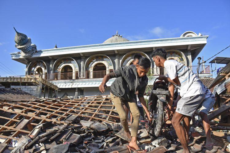Warga mengangkat sepeda motornya dari reruntuhan rumah pascagempa di Desa Wadon, Kecamatan Gunungsari, Lombok Barat, NTB, Senin (6/8/2018). Gempa bumi bermagnitudo 7 mengguncang Lombok, Minggu (5/8/2018) malam.