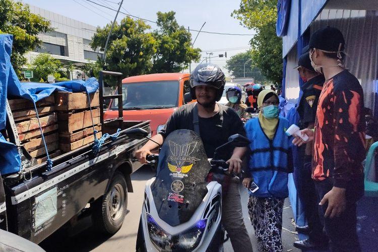 Seorang pengendara sepeda motor  tanpa mengenakan masker melintasi posko check point di Jalan Proklamasi Kota Tegal di hari pertama penerapan PSBB, Kamis (24/4/2020)