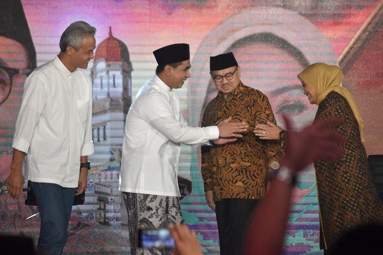 Calon gubernur Ganjar Pranowo (kiri) dan Sudirman Said (kedua kanan) menyaksikan calon wakil gubernur Taj Yasin (kedua kiri) dan Ida Fauziyah (kanan) berjabat tangan saat Debat Terbuka Pilkada Jawa Tengah di Ballroom Hotel Patra, Semarang, Jawa Tengah, Jumat (20/4/2018).
