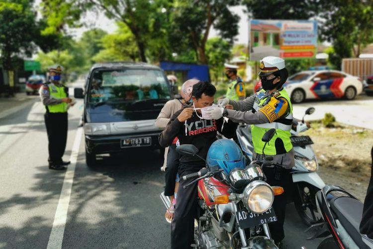 Petugas dari Satlantas Polres Karanganyar memakaikan masker kepada pengendara sepeda motor.