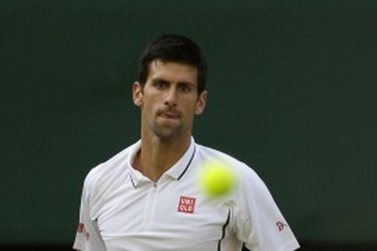 Petenis Serbia, Novak Djokovic, melihat bola yang dia mainkan bersama Tommy Haas dari Jerman. Mereka bertemu di babak keempat turnamen grand slam Wimbledon, Senin (1/7/2013).