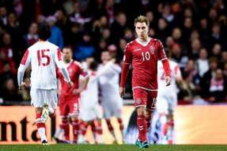 Gelandang Denmark, Christian Eriksen, tampak lesu ketika para pemain Montenegro merayakan gol ke gawang timnya, Selasa (11/10/2016).