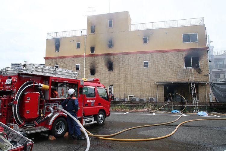 Truk pemadam kebakaran dan seorang petugas terlihat di luar gedung studio animasi berlantai tiga yang hangus terbakar di Kyoto, Jepang, Kamis (18/7/2019).