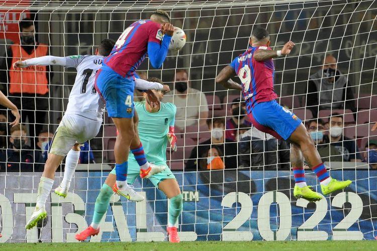 Bek Barcelona Ronald Araujo (kiri) menanduk bola yang berujung gol ke gawang Granada pada laga pekan kelima Liga Spanyol 2021-2022 di Stadion Camp Nou, Selasa (21/9/2021) dini hari WIB.