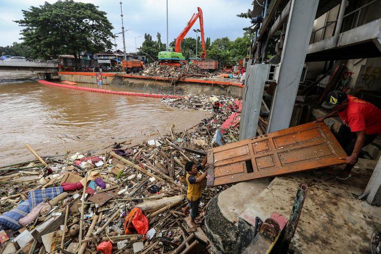 Warga menggambil pintu rumah yang terbawa arus di Pintu Air Manggarai, Jakarta, Rabu (7/2/2018). Dinas Lingkungan Hidup dan Kebersihan DKI Jakarta telah mengangkut 1.596 ton sampah yang hanyut akibat air kiriman dari Bendungan Katulampa, Bogor pasca banjir yang melanda Jakarta.