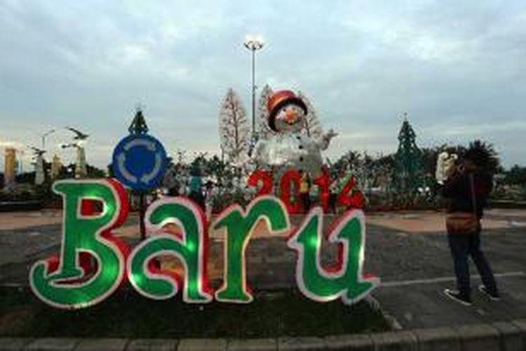 Pengunjung berfoto di ornamen Natal dan Tahun Baru 2014 yang dipajang di Bunderan Taman Impian Jaya Ancol, Jakarta Utara, Selasa (24/12/2013). Menjelang perayaan Tahun baru 2014, sejumlah tempat wisata memajang ornamen dan mengadakan berbagai program acara.