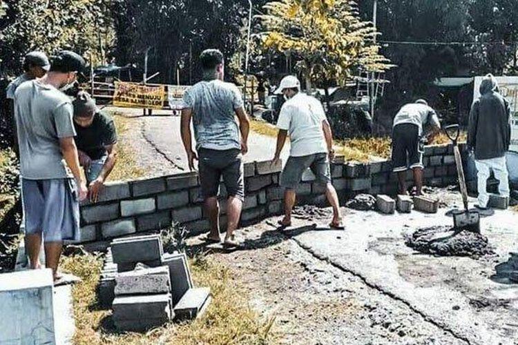 Pintu masuk Desa Sambigede dan Desa Senggreng di Kecamatan Sumberpucung, Kabupaten Malang, ditutup oleh warga dengan batako cor dan portal bambu, Minggu (10/5/2020).