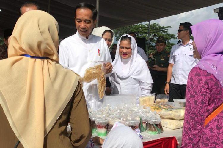 Presiden Joko Widodo dan Ibu Negara Iriana Jokowi saat membeli produk camilan milik ibu-ibu penerima program PNM Mekaar di Magetan, Jawa Timur, Jumat (1/2/2019).