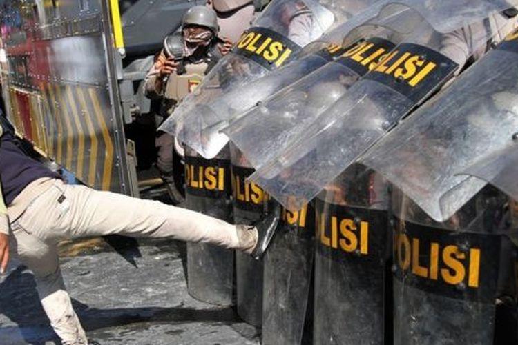 Pengunjuk rasa menendang barikade personel Polda Sulawesi Tenggara saat aksi menuntut penuntasan kasus kematian mahasiswa di depan Polda Sulawesi Tenggara, Kendari, Selasa (22/10).