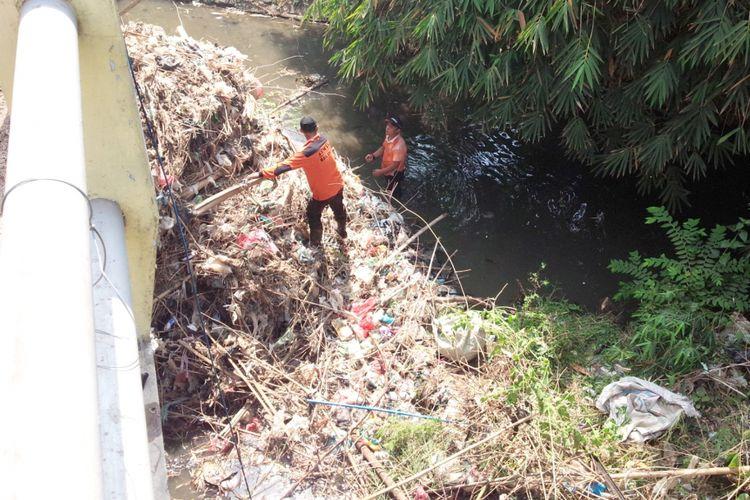 Para relawan membersihkan sampah yang menumpuk di bawah jembatan Kali Putih di Desa Selorejo, Kecamatan Mojowarno, Kabupaten Jombang, Minggu (04/11/2018).