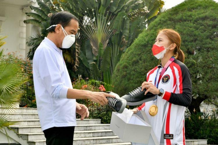 Presiden Joko Widodo melihat sepatu produk UMKM milik Greysia Polii usai menerima para atlet kontingen Indonesia untuk Olimpiade Tokyo 2020 di Istana Kepresidenan Bogor, Jumat (13/8/2021).