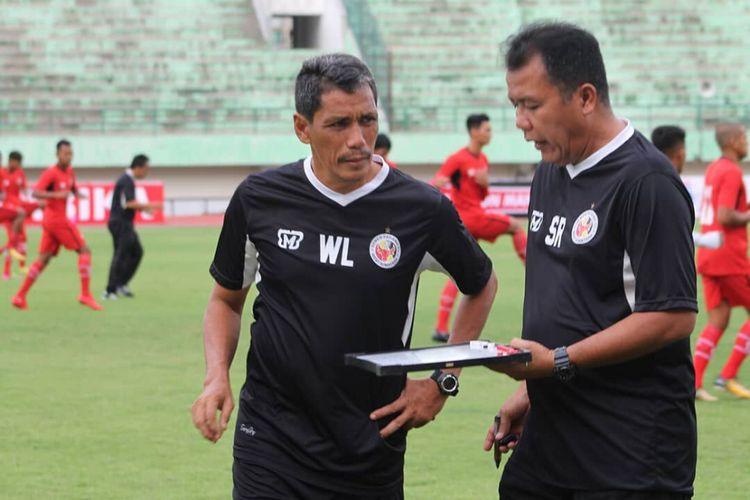 Pelatih Semen Padang Syafrianto Rusli berdiskusi dengan asistenya Welliansyah.