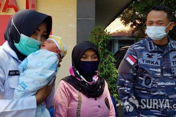 Bidan yang bertugas di Kantor Diskea Koarmada II, Indriyani menggendong bayi laki-laki yang berhasil ditolong dalam persalinan sungsang penuh risiko, Jumat (13/11/2020).