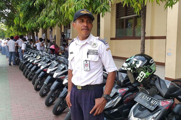 Satpam SMA Negeri 4 Tangerang Selatan, Slamet Gunaedi, berdiri di dekat barisan motor Honda BeAT, Senin (4/2/2019)