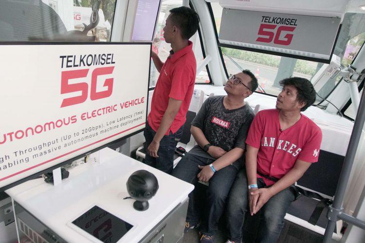 Sejumlah pengunjung saat mencoba kendaraan otonomos Navya di booth Telkomsel saat acara Asian Games di GBK Senayan, Jakarta, Kamis (23/08/2018). Mobil ini merupakan mobil tanpa awak pengemudi yang dihadirkan operator seluler Telkomsel selama acara Asian Games berlangsung.