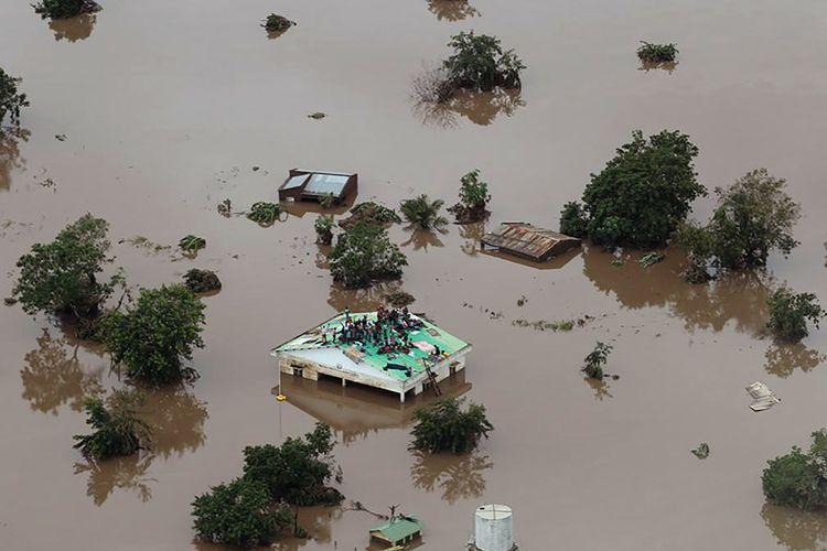 Orang-orang mengungsi dan tertahan di atap bangunan yang dikelilingi oleh banjir, di daerah yang terdampak topan Idai di Beira, Mozambik, Senin (18/3/2019). Ratusan orang tewas dan lainnya hilang di Mozambik dan Zimbabwe setelah topan Idai membawa serta banjir bandang dan angin kencang, 17 Maret lalu.