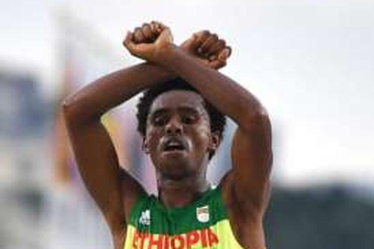 Feyisa Lilesa (26) membuat tanda 'X' dengan menggunakan kedua tangannya saat melintasi garis finis nomor maraton dalam Olimpiade Rio 2016. Tanda 'X' ini biasa digunakan etnis Oromo untuk menentang pemerintah Etiopia.