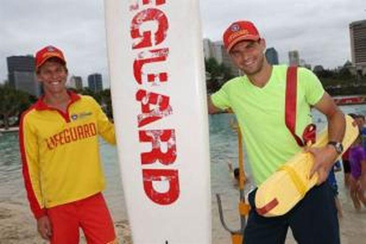 Petenis Bulgaria, Grigor Dimitrov (kanan) berpose bersama dengan penjaga pantai di pantai Brisbane, Selasa (31/12/2013)