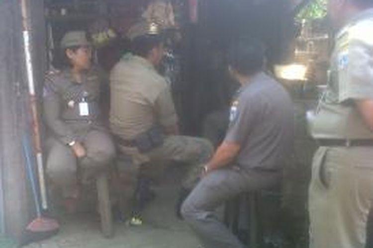 Petugas Satpol PP terlihat duduk-duduk saat penertiban Pasar Gembrong, Jakarta Timur, Rabu (14/8/2013). Sebab, tak ada pedagang yang menggelar lapak di badan jalan.