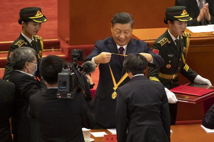 Presiden China Xi Jinping memberikan medali kepada salah satu dari empat pekerja medis dalam upacara penghormatan bagi mereka yang terlibat dalam perang melawan Covid-19 di Aula Agung Rakyat China di Beijing, pada Selasa 8 September 2020. Xi sekaligus menyatakan bahwa mereka berhasil melewati wabah virus corona yang luar biasa.