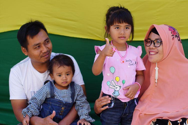 Salah satu anak yang akan menjalani pemotongan rambut gembel, Kayang Ayuningtiyas Nugroho (tengah), berfoto bersama keluarganya di rumah Tua Adat Ki Sumanto, di kawasan Dieng, Jawa Tengah, Sabtu (3/8/2019).
