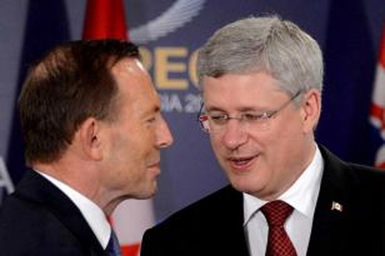 Perdana menteri Kanada Stephen Harper (kanan) berbicara dengan Perdana menteri Australia Tony Abbott dalam Asia-Pacific Economic Cooperation (APEC) di Bali, 7 Oktober 2013.