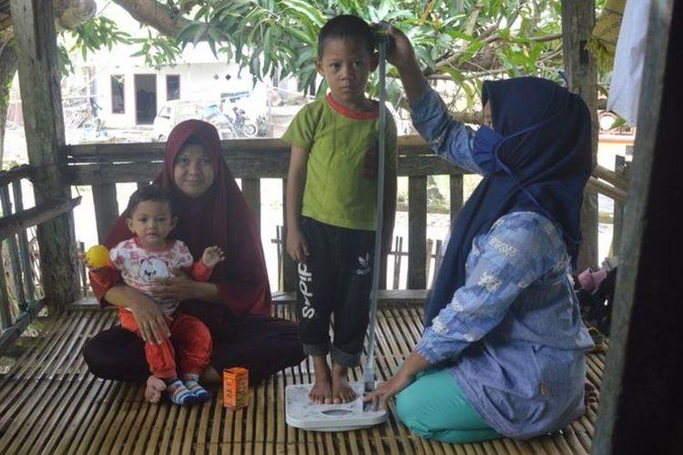 Kader Posyandu mendatangi rumah warga untuk mengukur tinggi badan dan penimbangan berat badan kepada dua balita penderita stunting di Kabupaten Takalar, Sulawesi Selatan. Kabupaten itu sukses menurunkan angka stunting dalam tiga tahun terakhir, namun kembali mencatat lonjakan di masa pandemi.