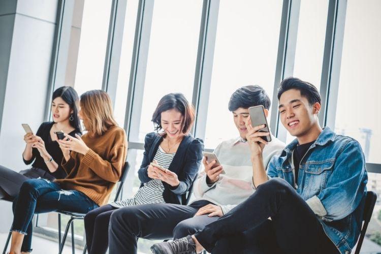Ilustrasi sekumpulan anak muda yang sedang memainkan media sosial menggunakan smartphone.