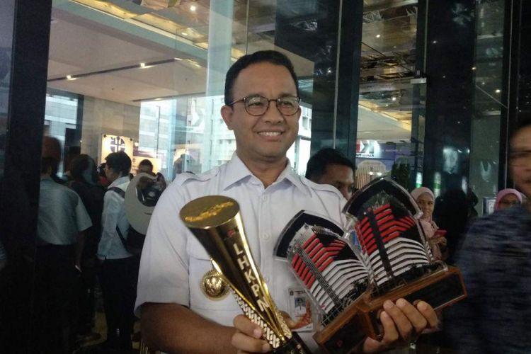 Gubernur DKI Jakarta Anies Baswedan menunjukkan piagam penghargaan yang diterima Pemprov DKI dari Komisi Pemberantasan Korupsi (KPK) di Hari Antikorupsi Sedunia (Hakordia) 2018 yang digelar di Hotel Bidakara, Jakarta Selatan, Rabu (5/12/2018)