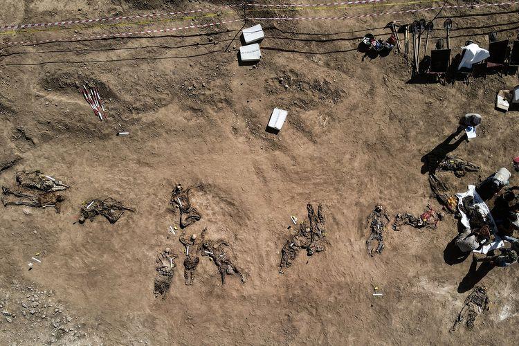 Foto udara yang diambil pada 13 Juni 2021 menunjukkan kerangka manusia yang diyakini korban ISIS dalam pembantaian Penjara Badush 2014 diangkat dari kuburan massal di sebelah barat laut Mosul, Irak. Di Juni 2014, anggota ISIS menyerang penjara itu, membawa hampir 600 tahanan yang mayoritas Syiah ke truk, membawa mereka ke sebuah jurang, dan membunuh mereka di sana.