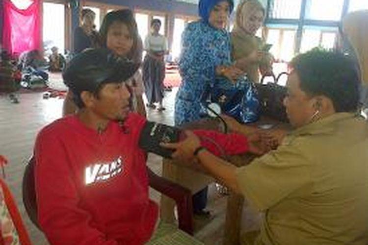Dokter dari Dinas Kesehatan Kota Kendari memeriksa seorang warga korban banjir yang mengungsi di posko gedung pemuda, Kendari?.