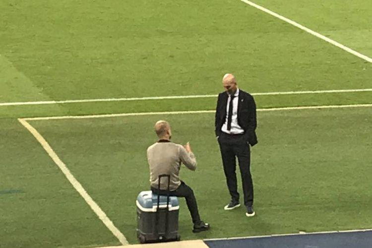 Pelatih Real Madrid, Zinedine Zidane, dan manajer Manchester City, Pep Guardiola, berbincang di pinggir lapangan seusai laga leg kedua babak 16 besar Liga Champions pada Sabtu (8/8/2020).